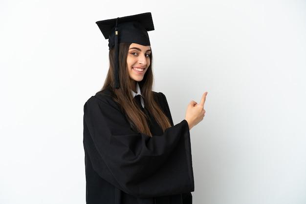 Jeune diplômé universitaire isolé sur fond blanc pointant vers l'arrière