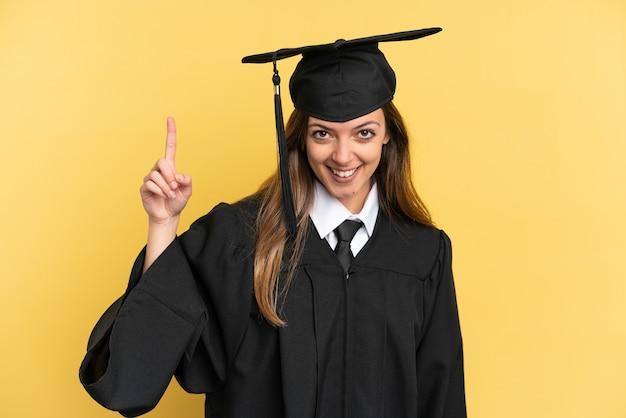 Jeune diplômé universitaire isolé sur fond jaune pointant vers une excellente idée