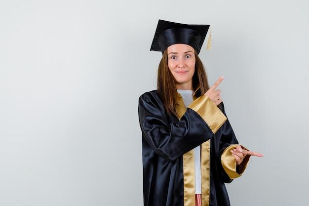 Jeune diplômée pointant de côté en tenue académique et à la recherche de confiance. vue de face.