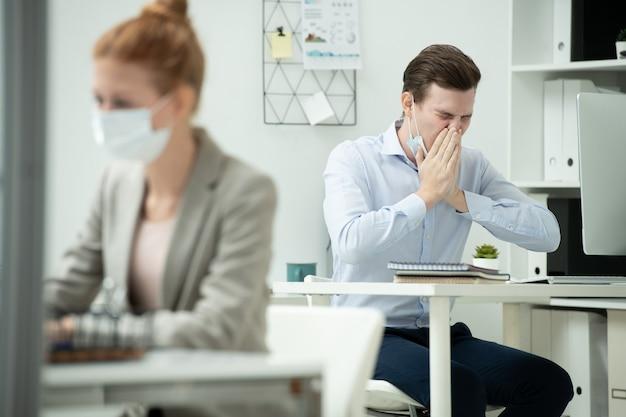 Jeune directeur de bureau masculin portant un masque de protection couvrant son nez et sa bouche à la main tout en éternuant sur le lieu de travail derrière une collègue