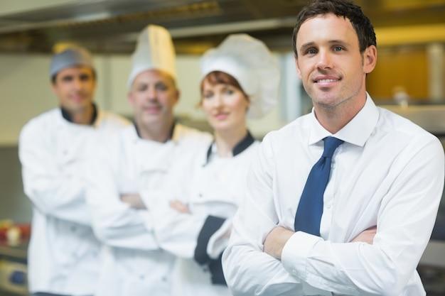 Jeune directeur de restaurant posant devant l'équipe
