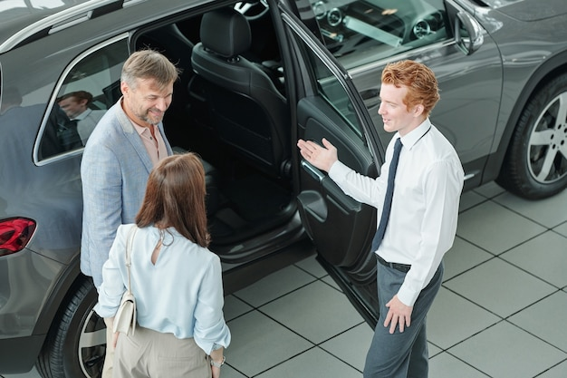 Jeune directeur des ventes élégant debout près de la porte ouverte d'une voiture noire et montrant aux clients l'intérieur tout en les consultant avant d'acheter