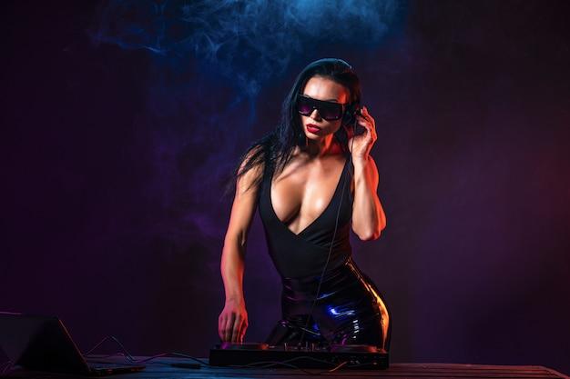 Jeune dj sexy avec des lunettes de soleil jouant de la musique