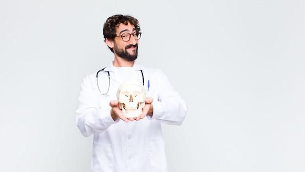 Jeune docteur barbu fou homme tenant un crâne humain