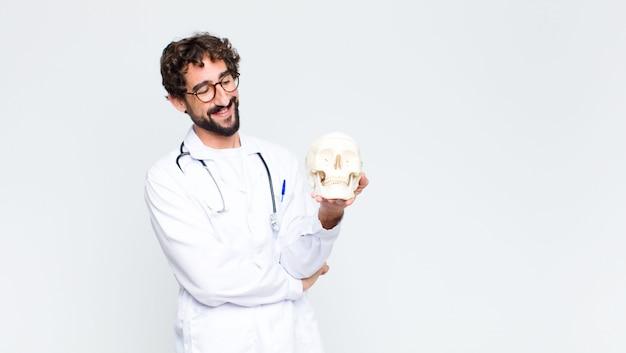 Jeune docteur barbu fou tenant un crâne humain
