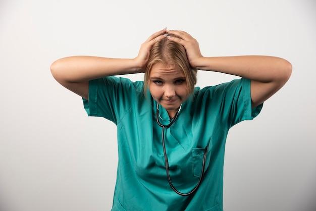 Jeune docteur troublé tenant sa tête sur le blanc.
