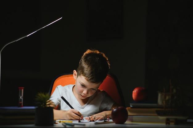 Jeune écolier adolescent à la table à faire ses devoirs dans la pièce sombre