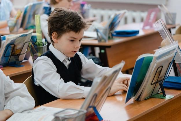 Le jeune écolier concentré en regardant le livre dans la salle de classe