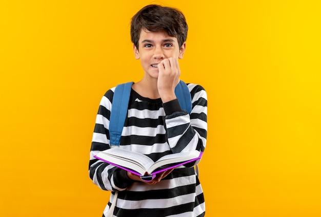 Un jeune écolier concerné portant un sac à dos tenant un livre mord les ongles isolés sur un mur orange