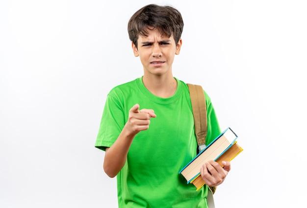Un jeune écolier confus portant un sac à dos tenant des livres pointe vers la caméra isolée sur un mur blanc