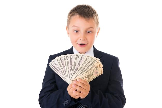 Jeune écolier entreprenant dans un costume d'affaires tenant de l'argent dans ses mains