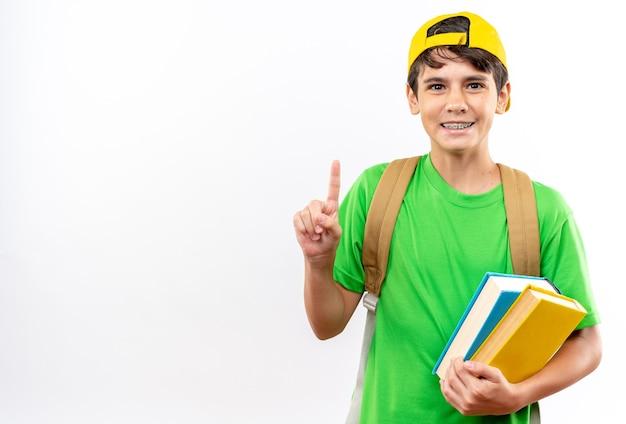 Un jeune écolier impressionné portant un sac à dos avec une casquette tenant des livres pointe vers le haut isolé sur un mur blanc avec un espace de copie