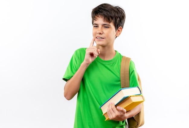Jeune écolier impressionné portant un sac à dos tenant des livres mettant le doigt sur la joue isolé sur un mur blanc