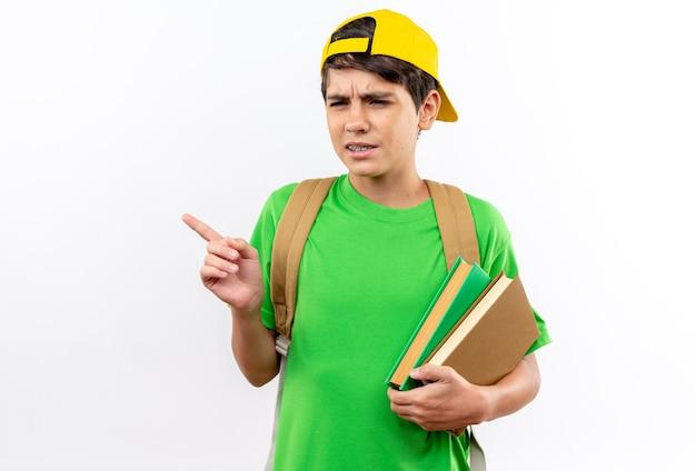 Jeune écolier mécontent portant un sac à dos avec une casquette tenant des livres sur le côté