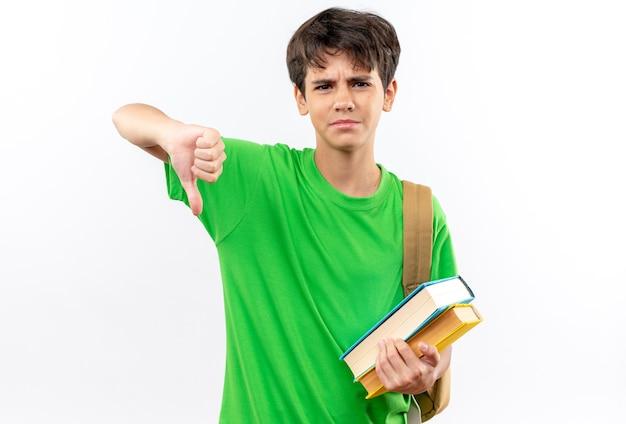 Jeune écolier mécontent portant un sac à dos tenant des livres montrant le pouce vers le bas