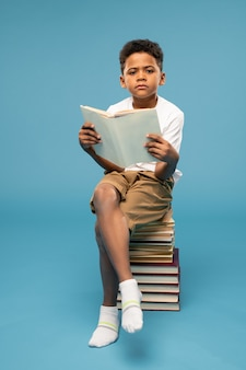 Jeune écolier sérieux en tenue décontractée et chaussettes blanches assis au sommet d'une grande pile de livres et lisant l'un d'entre eux