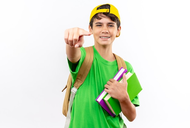 Jeune écolier souriant portant un sac à dos avec une casquette tenant des livres vous montrant un geste