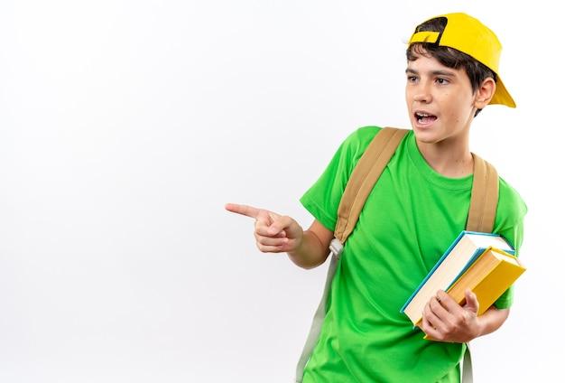 Jeune écolier surpris portant un sac à dos avec une casquette tenant des livres sur le côté isolé sur un mur blanc avec espace pour copie