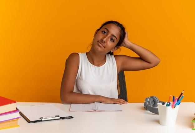 Jeune écolière assis au bureau avec des outils scolaires mettant la main sur la tête