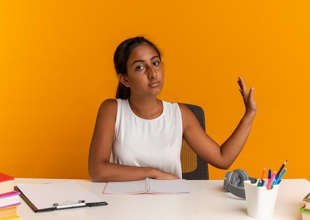 Jeune écolière assis au bureau avec des outils scolaires tenant main à côté