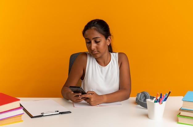 Jeune écolière assise au bureau avec des outils scolaires tenant et regardant le téléphone isolé sur le mur orange