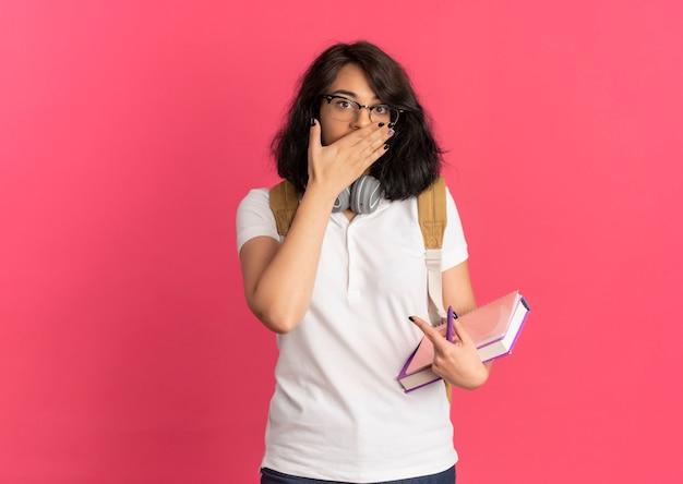 Jeune écolière caucasienne assez choquée avec des écouteurs sur le cou portant des lunettes et sac à dos met la main sur la bouche tenant des livres isolés sur l'espace rose avec copie