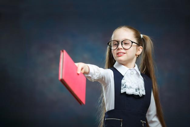 Jeune écolière passe tenir livre clin d'œil avec un œil