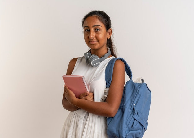 Jeune écolière portant un sac à dos et des écouteurs tenant un cahier sur blanc