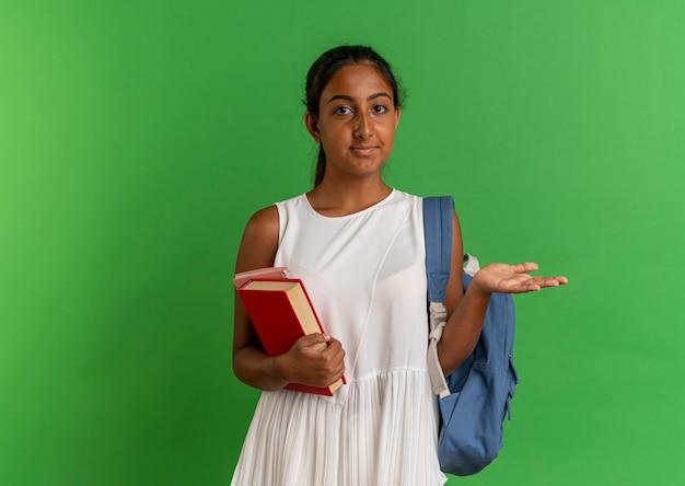 Jeune écolière portant sac à dos tenant livre avec ordinateur portable et montrant avec la main à côté