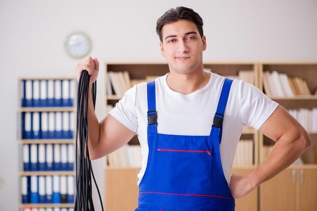 Jeune électricien avec câble travaillant au bureau