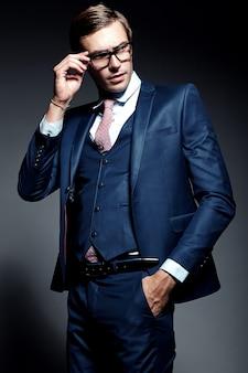 Jeune élégant modèle masculin beau homme d'affaires en costume bleu et lunettes à la mode, qui pose en studio
