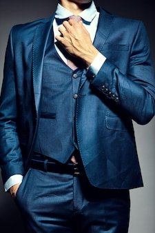 Jeune élégant modèle masculin beau homme d'affaires dans un costume attachant la cravate