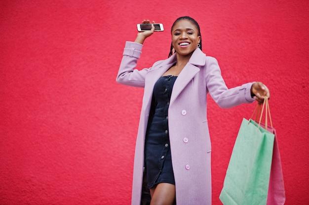 Jeune élégante belle femme afro-américaine sur fond de mur rouge, vêtue d'un manteau de tenue de mode avec des sacs à provisions et un téléphone portable à mains.