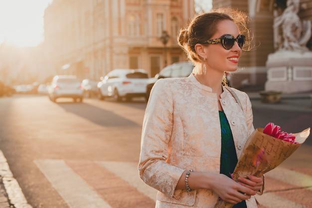 Jeune élégante belle femme marchant sur la rue de la ville au coucher du soleil