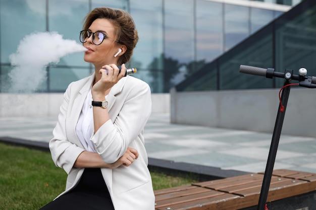 Jeune et élégante femme d'affaires fumant de la vape après son travail