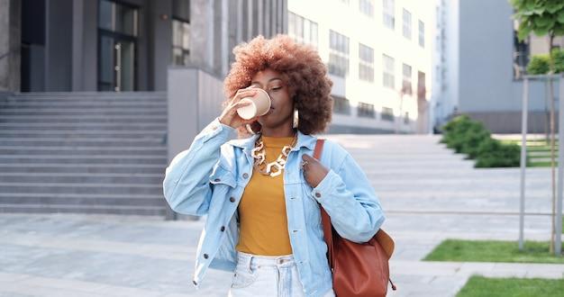 Jeune élégante femme afro-américaine belle bouclée avec sac marchant dans la rue de la ville, buvant du café à emporter et souriant joyeusement. femme assez heureuse se promener à l'extérieur et siroter une boisson chaude.