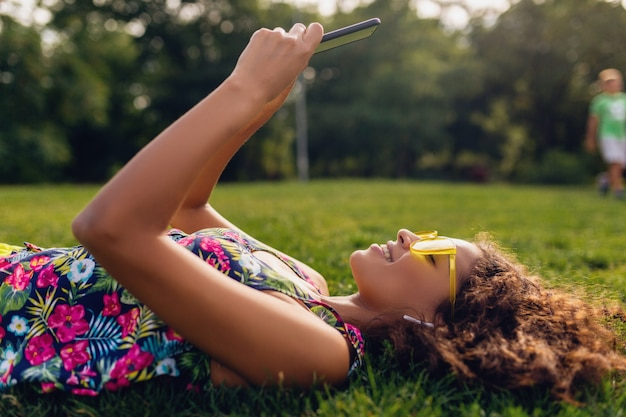 Jeune élégante femme noire souriante à l'aide de smartphone, écouter de la musique sur des écouteurs sans fil s'amuser dans le parc, style coloré de la mode d'été, allongé sur l'herbe, lunettes de soleil jaunes