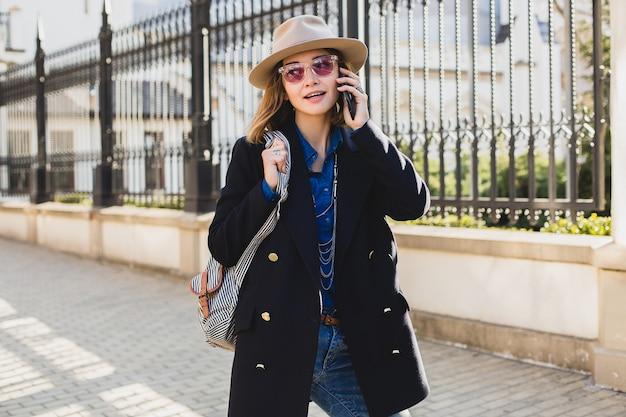 Jeune élégante jolie femme souriante, heureuse, surprise, parlant au téléphone, vêtue d'un manteau bleu foncé et d'une chemise en jean