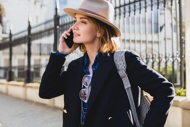 Jeune élégante jolie femme souriante et parler sur son téléphone, vêtue d'un manteau bleu foncé et d'un jean