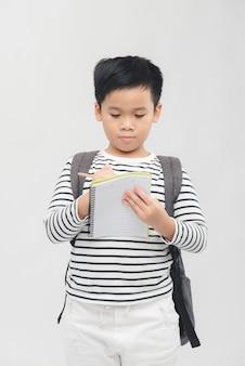 Jeune élève d'âge préscolaire portant un sac à dos et des cahiers - isolated over white