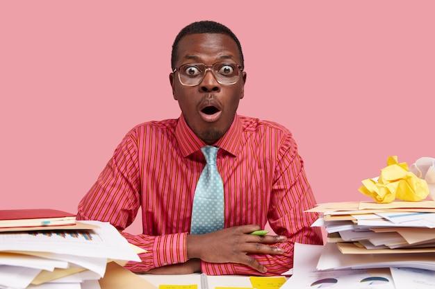 Un jeune employé alarmé et choqué fait des recherches sur le lieu de travail, entend quelque chose de terrible pendant le travail, habillé formellement