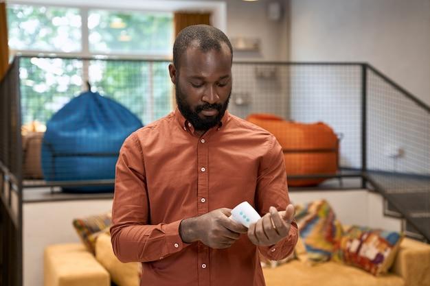 Jeune employé de bureau africain vérifiant la température avec un thermomètre infrarouge en se tenant debout dans le
