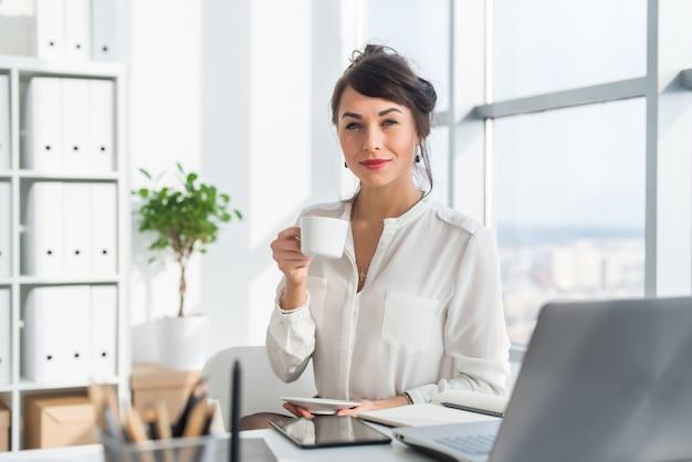 Jeune employé de bureau attrayant buvant une tasse de thé, prenant une pause-café le matin, se préparant pour la journée de travail.