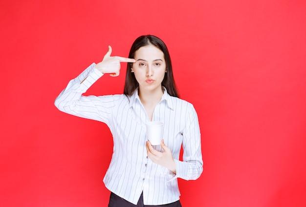 Jeune employé de bureau debout avec une tasse de thé en plastique sur un mur rouge.
