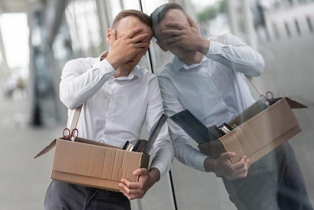 Un jeune employé de bureau licencié a cassé le verre d'un immeuble de bureaux moderne.