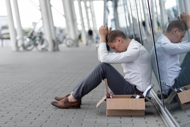 Un jeune employé de bureau licencié est assis sous son bureau. à côté de lui se trouve sa papeterie. l'homme est stressé.