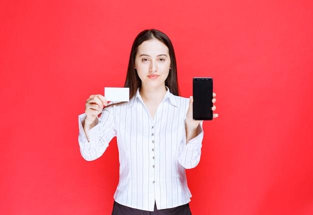 Jeune employé de bureau montrant une carte de visite et un téléphone portable.