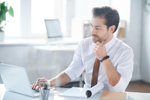Jeune employé de bureau sérieux se concentrant sur la recherche de données en ligne tout en planifiant le travail