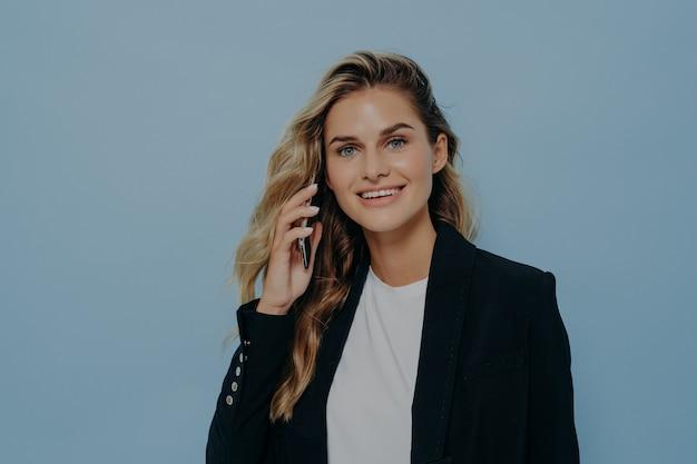 Jeune employé de bureau souriant et confiant parlant au téléphone portable, regardant directement la caméra tout en se tenant isolé sur fond bleu, portant un élégant blazer noir sur une chemise blanche