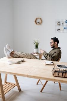 Jeune employé de bureau en tenue décontractée défilant dans le smartphone alors qu'il était assis sur le lieu de travail avec ses jambes sur la table